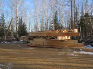 roof trusses in a pile, custom lake home, huisman concepts