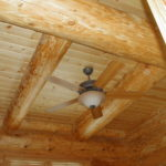 Ceiling fan between large log beams