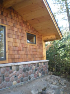 Log roof supports Stone and cedar Sauna building