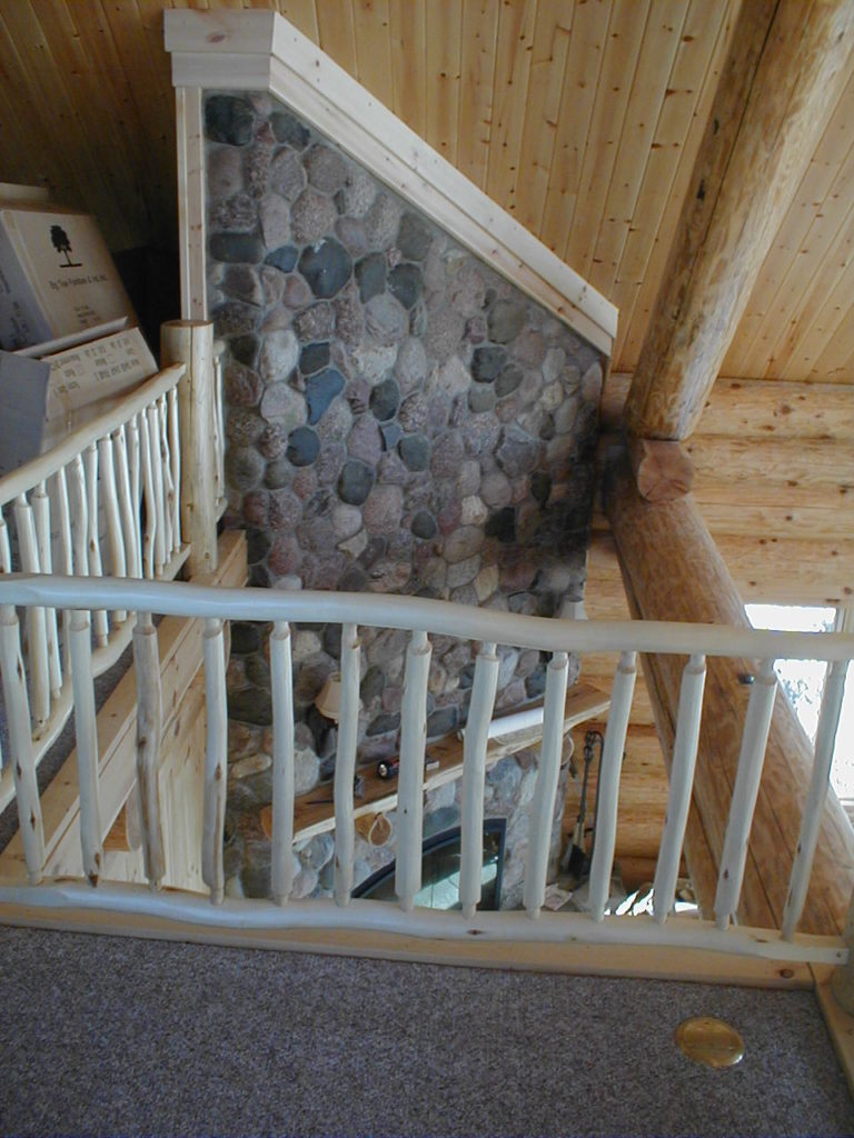 Fireplace from loft, rustic log railing