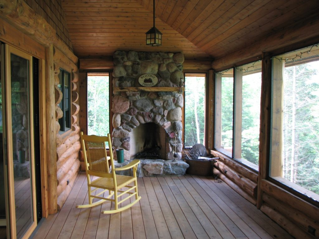The amazing screen porch with the rustic rock fireplace